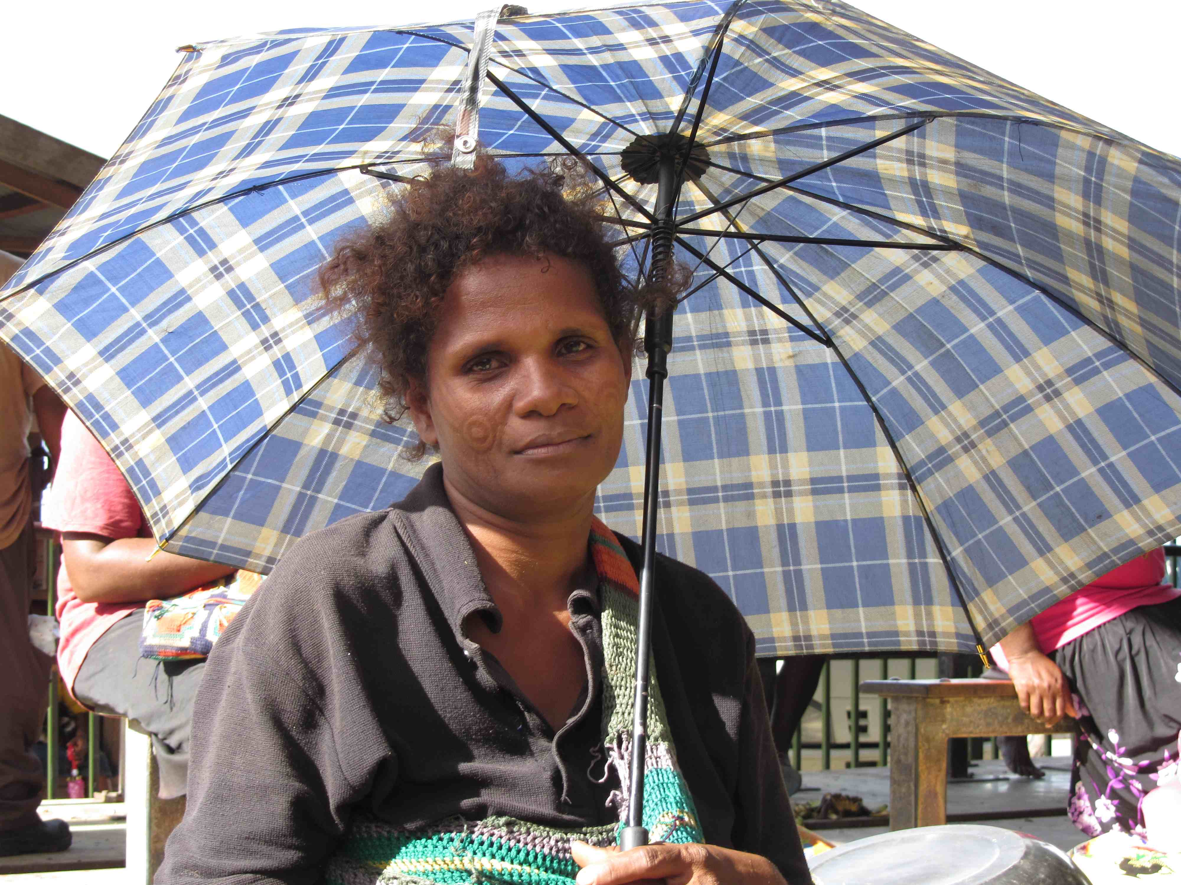 Beautiful banana seller seeks shade under umbrella, Central Market, Honiara, Solomon Islands